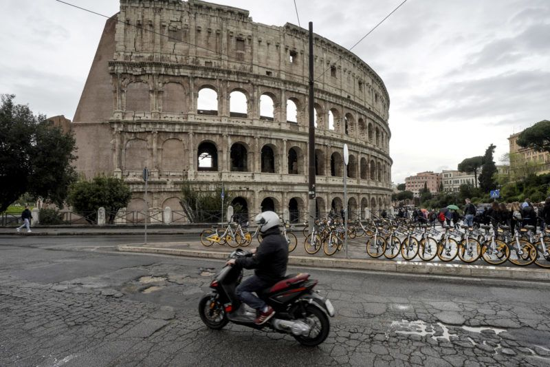 A motorcyclist rides over potholes on a road along the Colosseum in downtown Rome on April 12, 2018. - Rome's roads problems have been existing for years, due to structural failures as the city's basement is historically riddled with natural cavities. As a result, potholes range from a few centimeters deep to several meters that severely disrupt traffic and sometimes cause spectacular car accidents. (Photo by Andreas SOLARO / AFP)