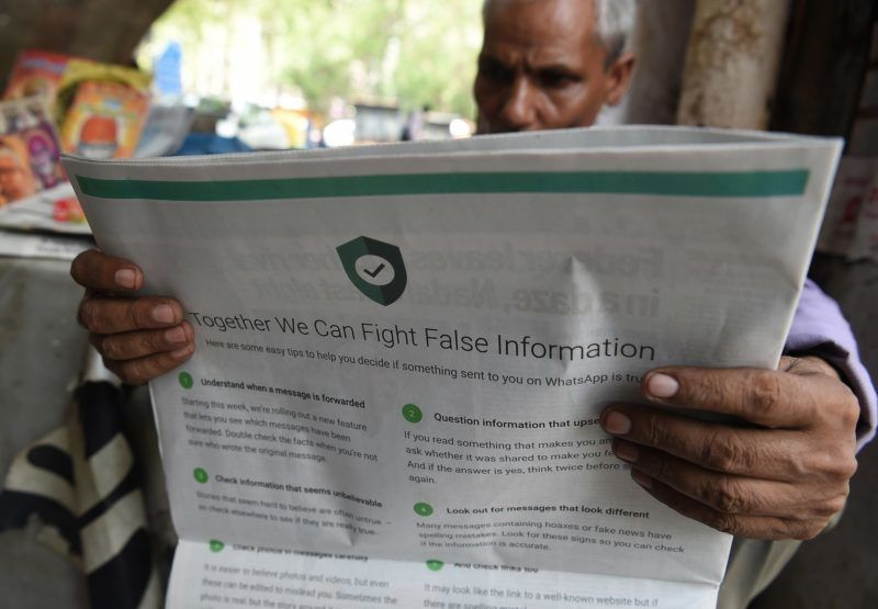 This photo illustration shows an Indian newspaper vendor reading a newspaper with a full back page advertisement from WhatsApp intended to counter fake information, in New Delhi on July 10, 2018. - Facebook owned messaging service WhatsApp on July 10 published full-page advertisements in Indian dailies in a bid to counter fake information that has sparked mob lynching attacks across the country. (Photo by Prakash SINGH / AFP)