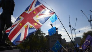 Demonstrators wave a Union flag and European Union flags as they take part in a march calling for a People's Vote on the final Brexit deal, in central London on October 20, 2018. - Britons dreading life outside Europe gathered from all corners of the UK to London on Saturday to try to stop their country's looming breakup with the EU. (Photo by NIKLAS HALLE'N / AFP)