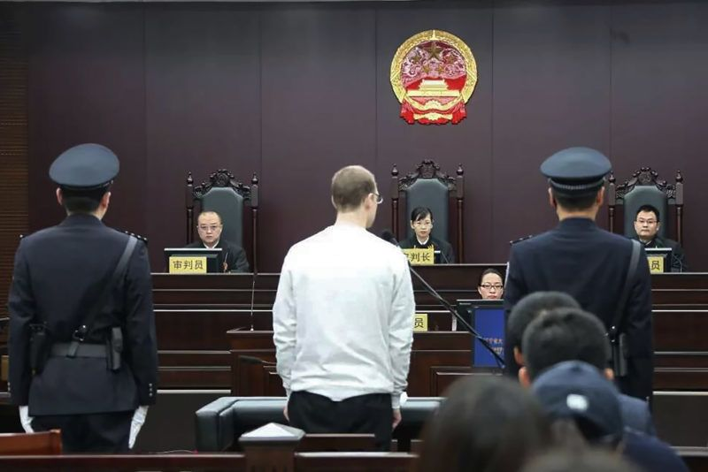 """This photograph taken and released by the Intermediate Peoples' Court of Dalian on January 14, 2019 shows Canadian Robert Lloyd Schellenberg (C) during his retrial on drug trafficking charges in the court in Dalian in China's northeast Liaoning province. - The court sentenced Schellenberg to death on drug trafficking charges on January 14, 2019 after his previous 15-year prison sentence was deemed too lenient, a ruling that has deepened a diplomatic rift between Ottawa and Beijing. (Photo by HANDOUT / Intermediate Peoples' Court of Dalian / AFP) / -----EDITORS NOTE --- RESTRICTED TO EDITORIAL USE - MANDATORY CREDIT """"AFP PHOTO / Intermediate Peoples' Court of Dalian"""" - NO MARKETING - NO ADVERTISING CAMPAIGNS - DISTRIBUTED AS A SERVICE TO CLIENTS - NO ARCHIVES"""