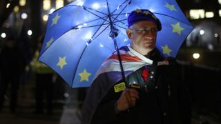 """A pro-EU supporter shelters under a European flag umbrella beside the Houses of Parliament in Westminster, central London on January 14, 2019. - Prime Minister Theresa May on Monday published further assurances from the EU on the eve of a crucial parliamentary vote on her Brexit deal and warned MPs that rejecting it would lead to """"paralysis"""" that could see Britain stay in the bloc. (Photo by Daniel LEAL-OLIVAS / AFP)"""