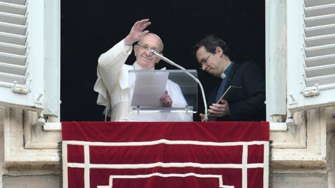 """Pope Francis waves after he invited the faithful to download the """"Click to Pray"""" app on a tablet computer (R), from the window of the Apostolic Palace overlooking St. Peter's square in the Vatican during the weekly Angelus prayer on January 20, 2019. - As Pope Francis is to make his first trip to Panama on January 23 for a gathering of more than 150,000 young Catholics from across the globe at the World Youth Day festival, he invited the faithful to downnload """"Click to Pray"""" an application that allows believers to unite their prayers online with the Pope every day. (Photo by Vincenzo PINTO / AFP)"""