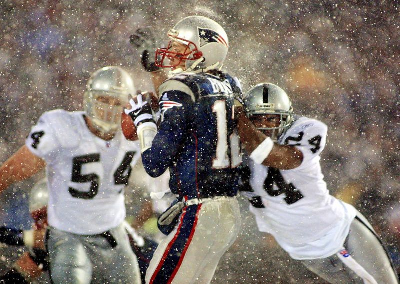 New England Patriots  quarterback Tom Brady (C) takes a hit from Charles Woodson (R) of the Oakland Raiders on a pass attempt in the last two minutes of the game in their AFC playoff 19 January 2002 in Foxboro, Massachusetts.  The Patriots won 16-13 in overtime. AFP PHOTO/Matt CAMPBELL (Photo by MATT CAMPBELL / AFP)