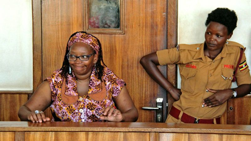 """University lecturer and activist Doctor Stella Nyanzi (L) reacts in court as she attends a trial to face charges for cyber-harassment and offensives communication, in Kampala, on April 10, 2017. - Nyanzi appears to court charged with cyber-harassment and offensives communication by using her Facebook account to disturb President Museveni's privacy after calling him a """"pair of buttocks"""" in a Facebook post. Nyanzi shot to prominence on April 2016 when she stripped naked at her university to protest the closure of her office, and later shared the nude photos of herself on social media. (Photo by GAEL GRILHOT / AFP)"""