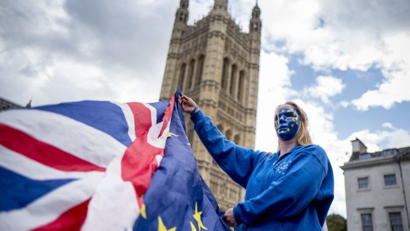 A Pro-European Union protester holds Union and European flags in front of the Victoria Tower at The Palace of Westminster in central London on September 13, 2017, ahead of a rally to warn about the terms of Brexit, by EU nationals in Britain and UK nationals in Europe. (Photo by Tolga AKMEN / AFP)