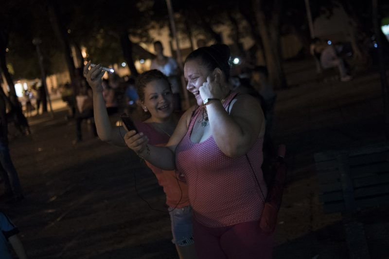 HAVANA, CUBA - SEPTEMBER 23:  A woman uses her mobile phones to connect to the internet and speak with her relativies abroad while her daughter illuminates her face with her mobile in a public square with Wifi conectivity to the internet in Central Havana on september 23, 2015. Cuban People use the internet communications to get in contact with their families abroad and also for social media despite not all internet services are available in Cuba. Carlos Becerra / Anadolu Agency