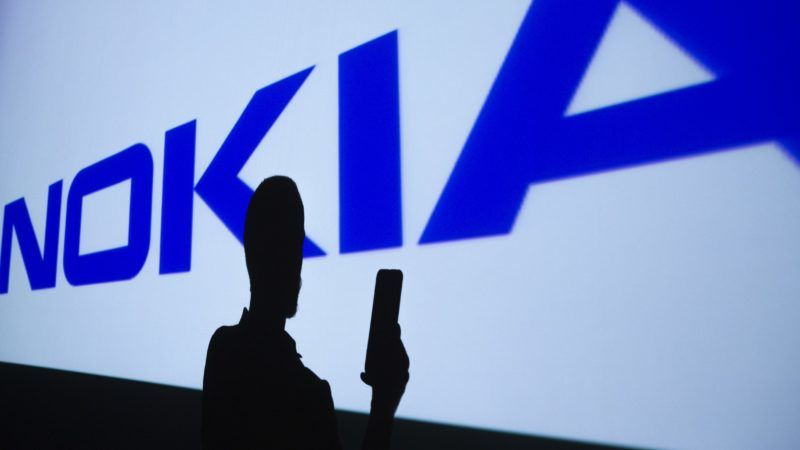 ANKARA, TURKEY - JULY 26 : A person holding a mobile phone stands in front of a projector showing the logo of NOKIA in Ankara, Turkey on July 26, 2018.  Aytac Unal / Anadolu Agency