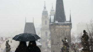 Tourists walk across the Charles Bridge as snow falls in Prague on March 6, 2018. (Photo by Michal Cizek / AFP)