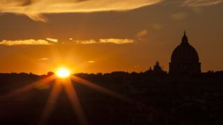 The sun sets over Rome and St Peter's Basilica at the Vatican (rear R) on January 1, 2019 as seen from Pincio Hill. (Photo by Laurent EMMANUEL / AFP)
