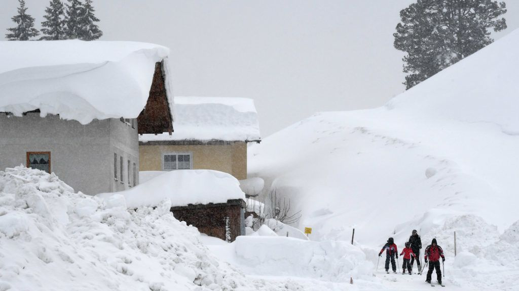 Skiers make their way through the streets after heavy snowfall in the small village of Filzmoos, Austria, on January 7, 2019. (Photo by Christof STACHE / AFP)