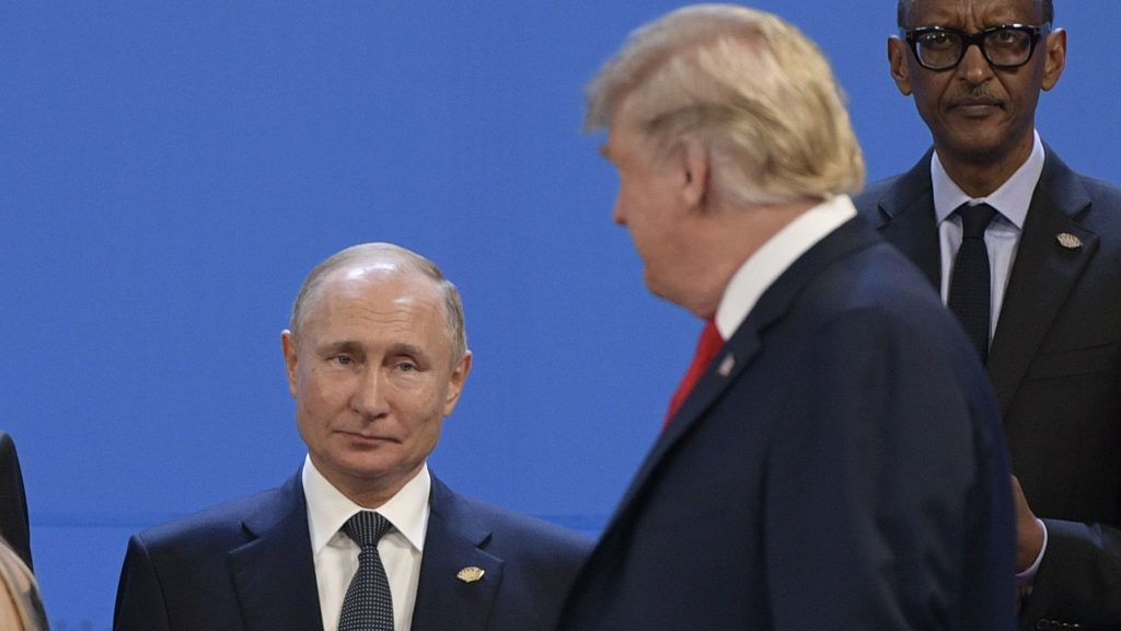 (FILES) In this file photo taken on November 30, 2018 US President Donald Trump(R), looks at Russia's President Vladimir Putin as they take place for a family photo, during the G20 Leaders' Summit in Buenos Aires. - The Federal Bureau of Investigation opened an inquiry in 2017 into whether US President Donald Trump was working on behalf of Russia, The New York Times reported on January 11, 2019. The investigation -- a dual counterintelligence and criminal probe -- was launched after the president fired FBI director James Comey in May 2017, the Times said, citing anonymous sources. (Photo by Juan MABROMATA / AFP)