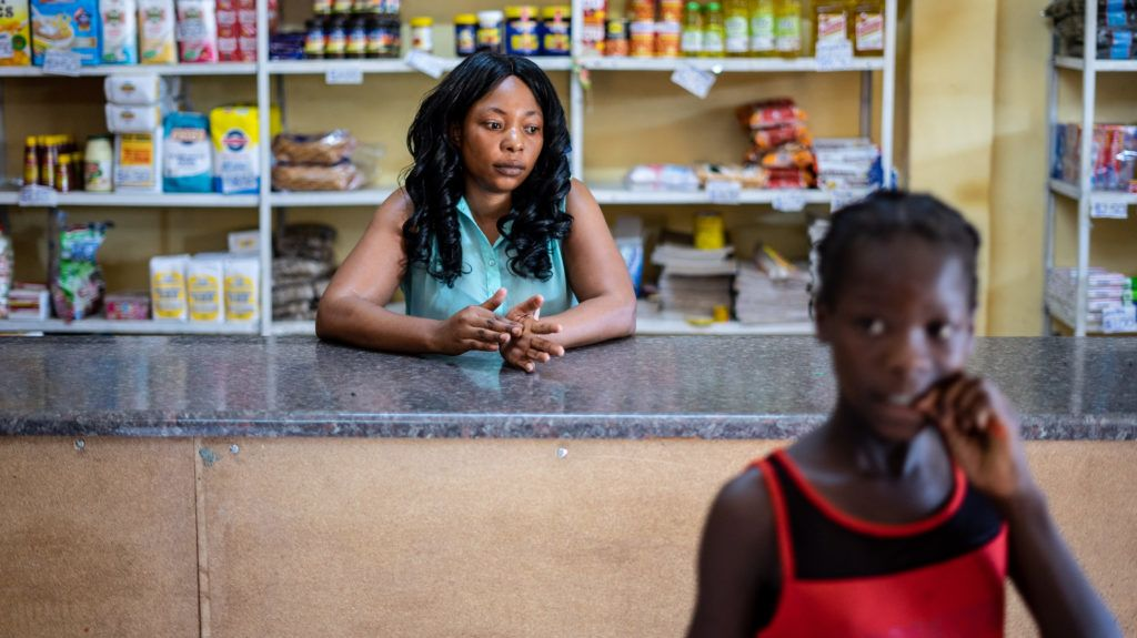Grocery store assistant Lilian waits for customers inside a shop in Rimuka township, Kadoma on January 24 2019. - In the central Zimbabwean town of Kadoma, it is now a daily routine -- armed soldiers and police patrolling through the quiet back streets as residents hide indoors. A price hike unleashed anger over the country's latest economic woes, which have worsened despite Mnangagwa's promises of a fresh start and a revived economy after former President Mugabe's downfall. (Photo by ZINYANGE AUNTONY / AFP)