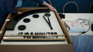 """The Doomsday clock is seen after members of the Bulletin of the Atomic Scientists moved it 30 seconds closer to the end of the world January 25, 2018 in Washington, DC. - Mounting concerns about the possibility of a nuclear war along with US President Donald Trump's """"unpredictability"""" have pushed the symbolic """"Doomsday Clock"""" to two minutes before midnight, the Bulletin of Atomic Scientists said Thursday. The clock -- which serves as a metaphor for how close humanity is to destroying the planet -- was moved forward by 30 seconds, to as near as it has ever been to the hour of the apocalypse. (Photo by Brendan Smialowski / AFP)"""