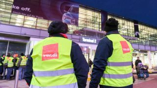 15 January 2019, Bavaria, München: Employees are standing in front of Terminal 2 at Munich Airport (Bavaria). Verdi has called on the employees of the goods and employee control department at the airport to go on a warning strike. Photo: Tobias Hase/dpa