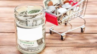 Dollar bills in glass jar with blank label and shopping cart with money on the wooden table.