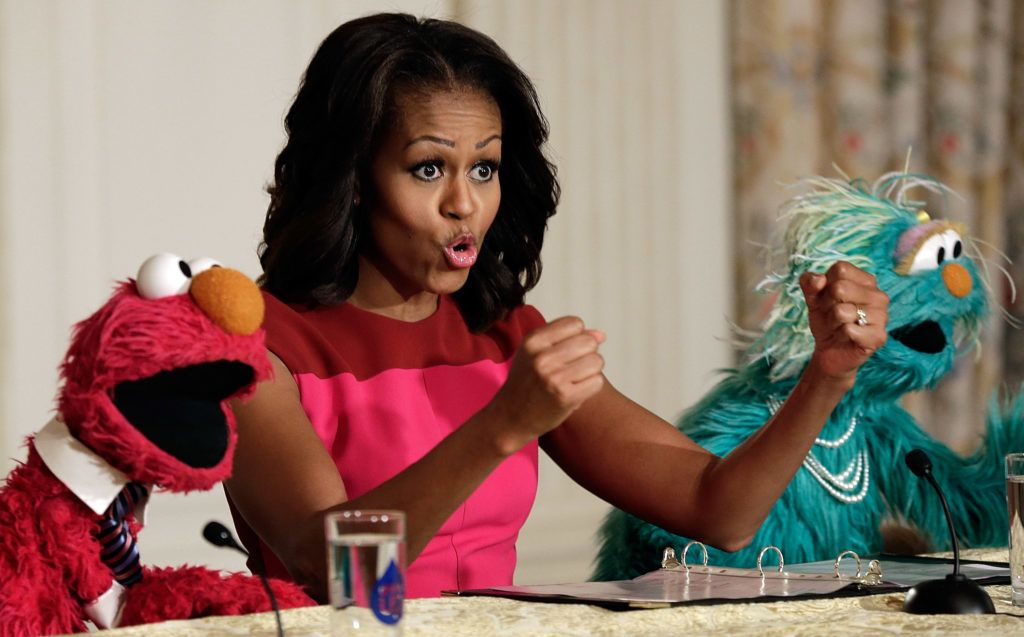 WASHINGTON, DC - OCTOBER 30:  U.S. first lady Michelle Obama joins with Sesame Street's Elmo (L) and Rosalita (R) for an announcement on a new initiative aimed at promoting healthier nutrition for school children Ocotber 30, 2013 in Washington, DC. During the event the first lady announced that Sesame Street characters will join with the Partnership for a Healthier America in a two-year agreement to promote greater fresh fruit and vegetable consumption by children.  (Photo by Win McNamee/Getty Images)