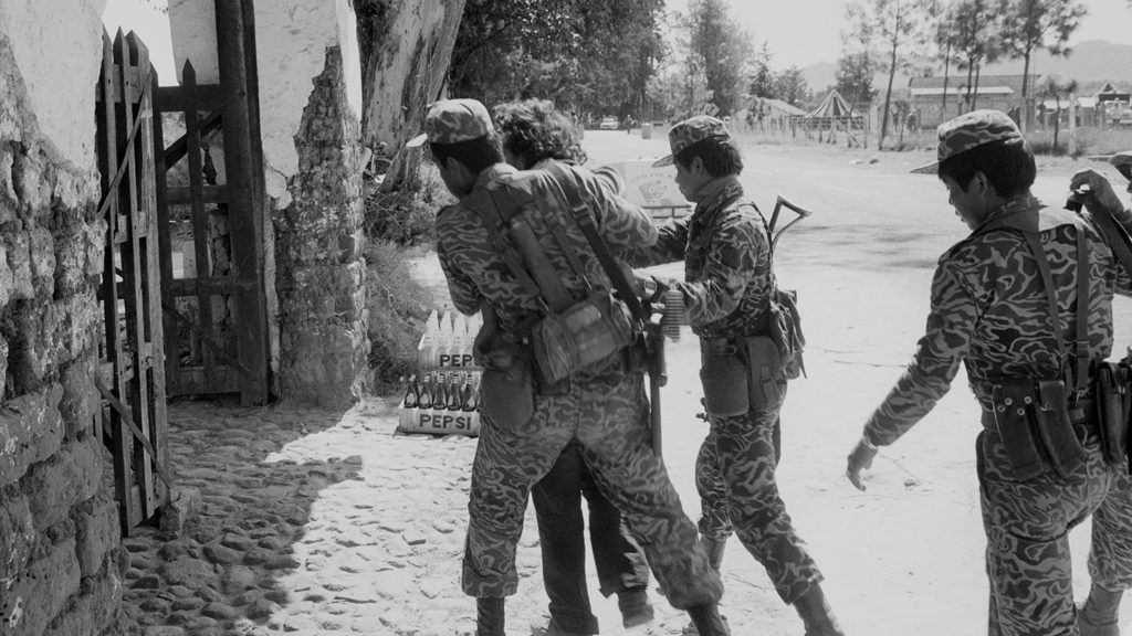 SANTA CRUZ DEL QUICHE, GUATEMALA - JANUARY 1: Army soldiers direct a suspected leftist guerrilla into a building for interrogation in the military compound January 1, 1982 in Santa Cruz del Quiché, Guatemala. Over 200,000 people were killed in the country's 36-year civil war and 45,000 people disappeared.  (Photo by Robert Nickelsberg/Getty Images)