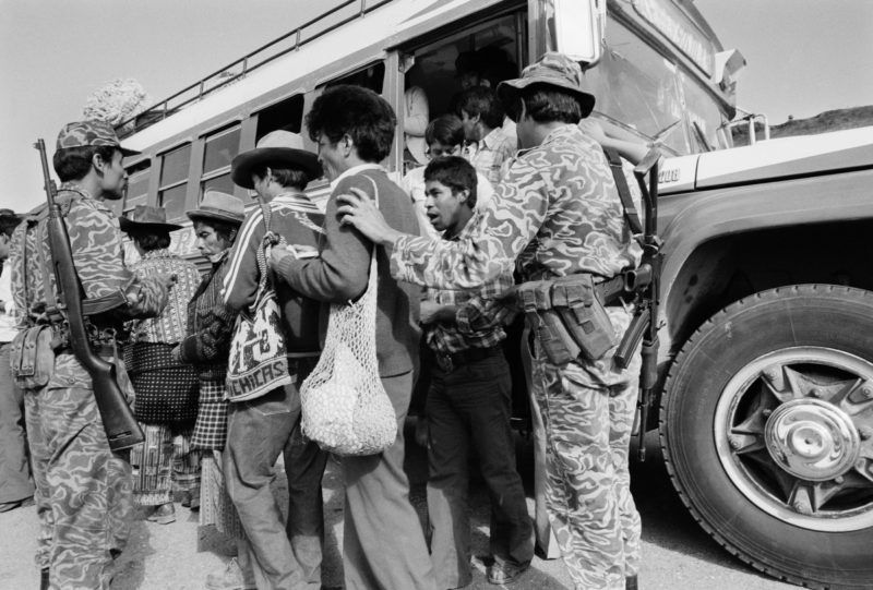 CHICHICASTENANGO, GUATEMALA - MARCH 1: Army soldiers check identity cards of bus passengers March 1, 1982 along the Pan American Highway to Chichicastenango, Guatemala. The Guatemalan army had initiated a brutal counterinsurgency program targeting the Mayan Indian population of the highlands and urban areas as the General Lucas Garcia government fought off a leftist insurgency of armed guerrilla groups. (Photo by Robert Nickelsberg/Getty Images)