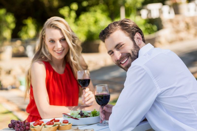 Portrait of happy couple holding wine glasses in the restaurant