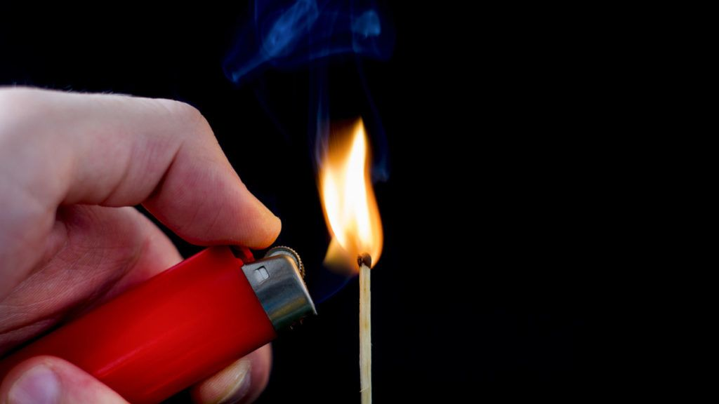 Man hand with lighter start light on Matchstick  isolated on black, close up. Studio shoot image.