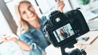 Beautiful young woman in casual wear smiling while recording video