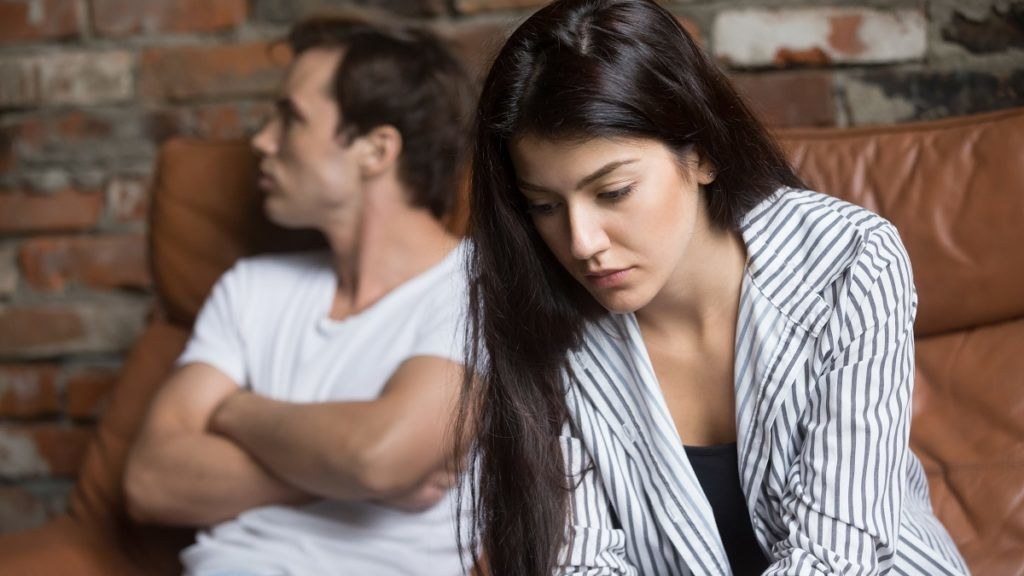 Sad pensive young girl thinking of relationships problems sitting on sofa with offended boyfriend, conflicts in marriage, upset couple after fight dispute, making decision of breaking up get divorced
