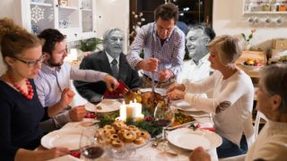 Beautiful big family sitting at the table celebrating Christmas together at home. Father cutting and serving roasted turkey.