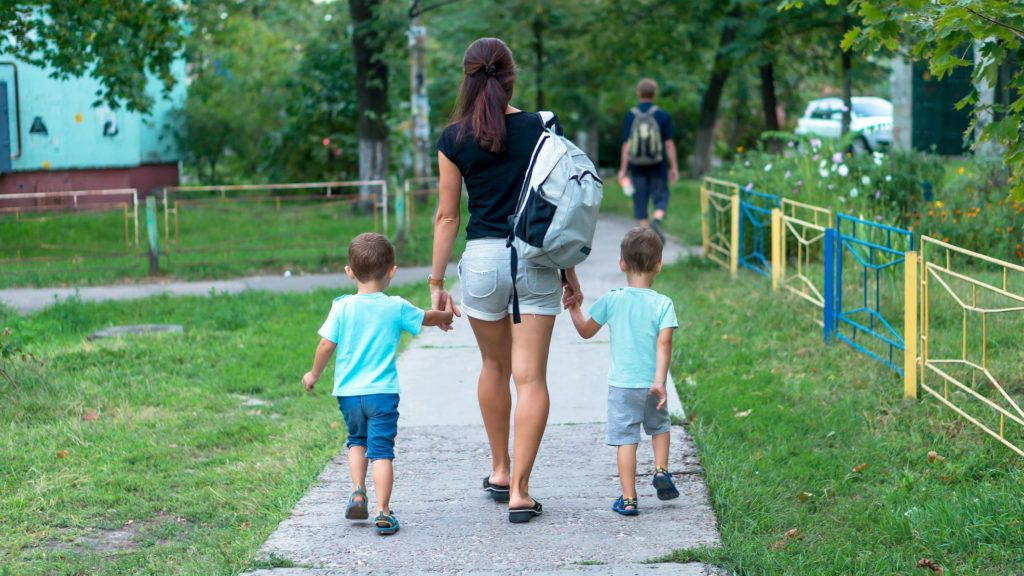 Young mother walking and holding hands two boys