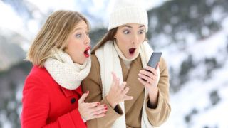 Two amazed friends with a smart phone in winter holidays in a snowy mountain