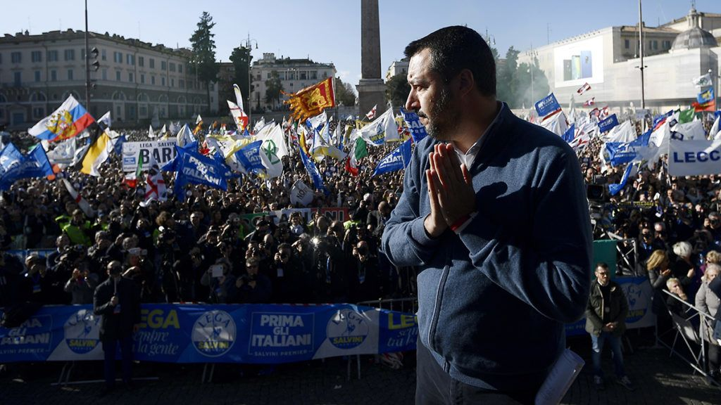 """Lega party leader and Interior Minister Matteo Salvini (C) waves to supporters during a protest against European Union officials at Piazza del Popolo on December 8, 2018 in Rome. - Salvini spoke to thousands of supporters in a packed square in Rome  as his surging League party celebrates six months in power. Organisers said around 80,000 people attended -- many travelling from around the country -- waving flags and banners with slogans such as """"Italians first"""", """"Italy raises its head"""" and """"Six months of common sense government"""". (Photo by FILIPPO MONTEFORTE / AFP)"""