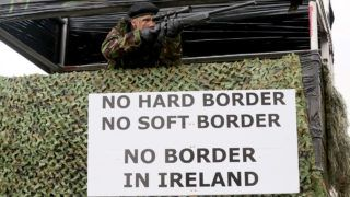 """Members of the anti-brexit campaign group """"Border communities against Brexit"""", dressed as British Army Soldiers, pose with a wall installed on a road crossing the border between Northern Ireland and Ireland, during a demonstration in Newry, Northern Ireland, on January 26, 2019, near the Irish border. - Keeping the Irish border free-flowing has proved to be the toughest issue to resolve in negotiating Britain's exit from the European Union. The Brexit deal between London and Brussels -- overwhelmingly rejected last week by British MPs -- contains a so-called backstop provision ensuring that if all else fails, the border will remain open. (Photo by Paul FAITH / AFP)"""