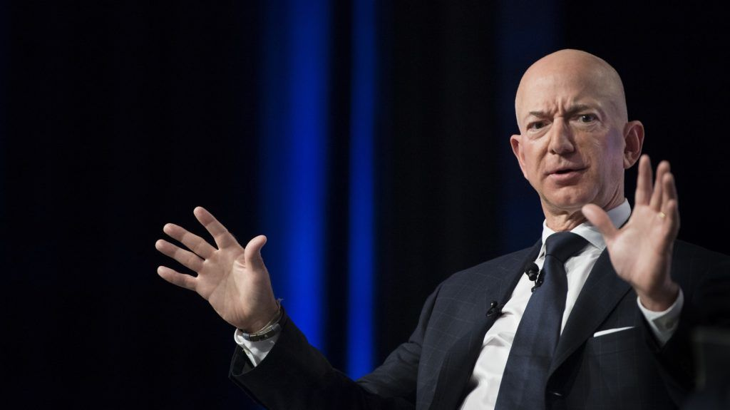 """(FILES) In this file photo taken on September 19, 2018 Amazon and Blue Origin founder Jeff Bezos provides the keynote address at the Air Force Association's Annual Air, Space & Cyber Conference in Oxen Hill, MD. - Amazon CEO Jeff Bezos on February 7, 2019 accused the publisher of the National Enquirer of """"blackmail"""" after it threatened to publish intimate photographs sent by the billionaire to his mistress. (Photo by Jim WATSON / AFP)"""