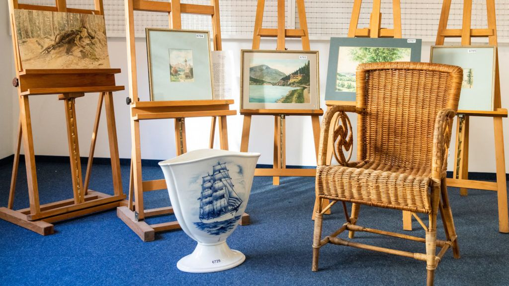 """A picture taken on February 8, 2019 at the Weidler auction house in the southern German city of Nuremberg shows a wicker armchair, bearing a swastika, a vase and watercolours which are presumed to have belonged to late Nazi dictator Adolf Hitler. - A German auction house scrapped the planned sale of 26 artworks attributed to Adolf Hitler, after doubts emerged about their authenticity just days before they were due to go under the hammer. Five paintings signed """"A. Hitler"""", all of them watercolours, will be auctioned off on February 9, 2019 as scheduled, according to the Weidler auction house. (Photo by DANIEL KARMANN / AFP)"""