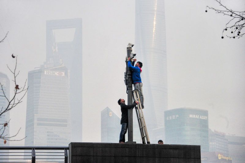 Chinese workers check surveillance cameras on the Bund as the Shanghai Tower, tallest, the Shanghai World Financial Center, second tallest, and other high-rise buildings and skyscrapers are seen vaguely in heavy smog in Shanghai, China, 30 January 2018.  