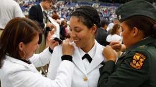 ANNAPOLIS, MD - MAY 28: U.S. Navy Academy graduate Angelique Wiley (C) has her collar insignias put on by her sister Nadine Wiley (R), a member of the Temple University ROTC, and her mother U.S. Army Lt. Col. Rita Wiley (L) at the conclusion of the graduation ceremony at the academy May 28, 2010 in Annapolis, Maryland. During the Naval Academy's 160th traditional graduation ceremony, 1,028 midshipmen, including 219 women, earned their commissions.   Chip Somodevilla/Getty Images/AFP