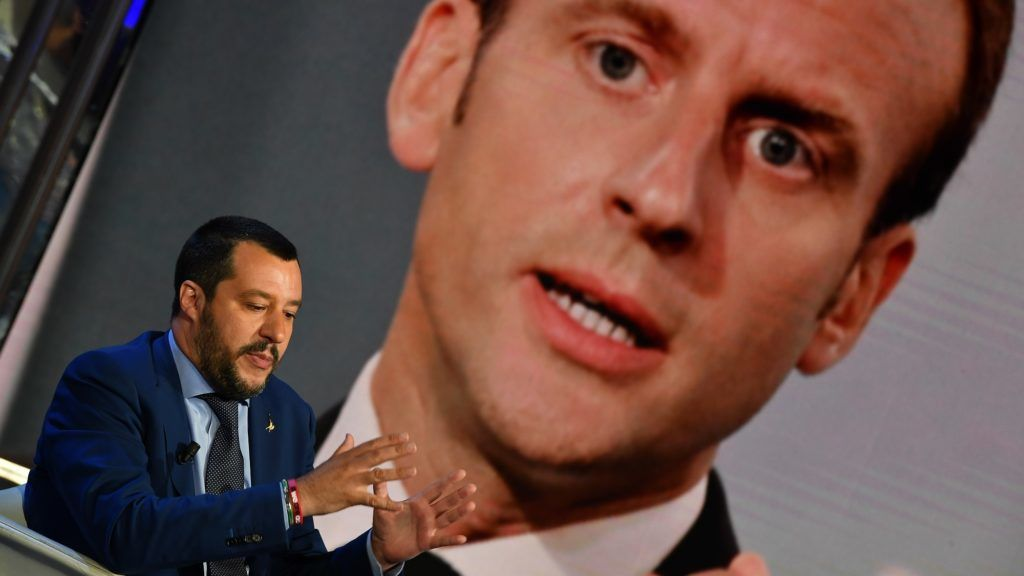 """Italy's Interior Minister and Deputy Prime Minister Matteo Salvini gestures as he speaks during the Italian talk show """"Porta a Porta"""", broadcast on Italian channel Rai 1, in Rome, on June 20, 2018, as a picture of French President Emmanuel Macron is seen in the background. (Photo by Andreas SOLARO / AFP)"""