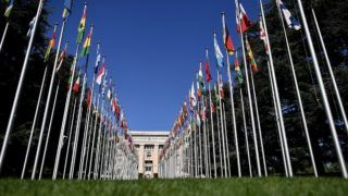 """The """"Palais des Nations"""", which houses the United Nations Offices, is seen at the end of the flag-lined front lawn on September 4, 2018 in Geneva. (Photo by Fabrice COFFRINI / AFP)"""
