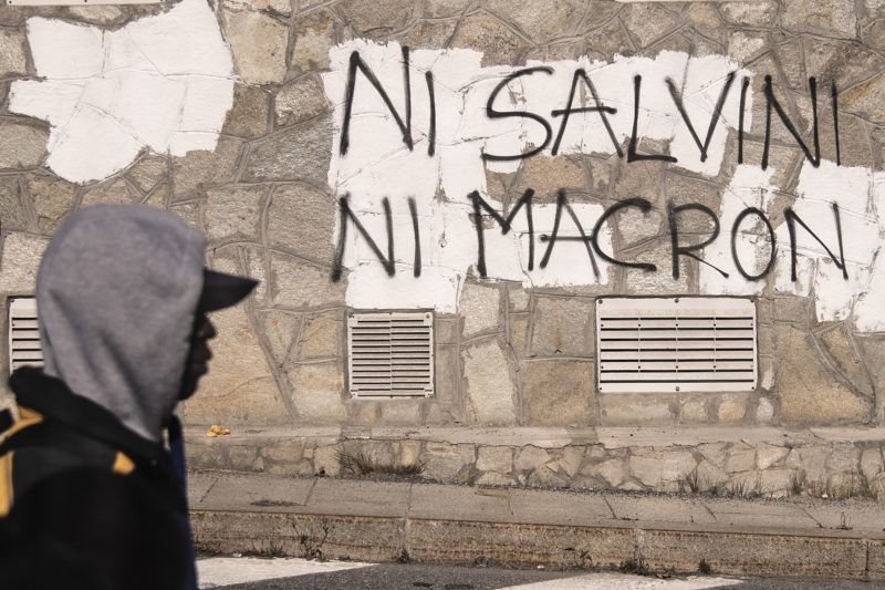 """A migrant walks past an inscription reading, in French, """"Neither Salvini, nor Macron"""" on October 21, 2018 in the Alpine border town of Claviere, some 100 kilometers west of Turin. - Italy's Interior minister Matteo Salvini sent police on October 20 to Claviere, following an ongoing argument with French authorities over the alleged return of migrants deposed by French police on the Italian side of the border in Claviere. (Photo by MARCO BERTORELLO / AFP)"""