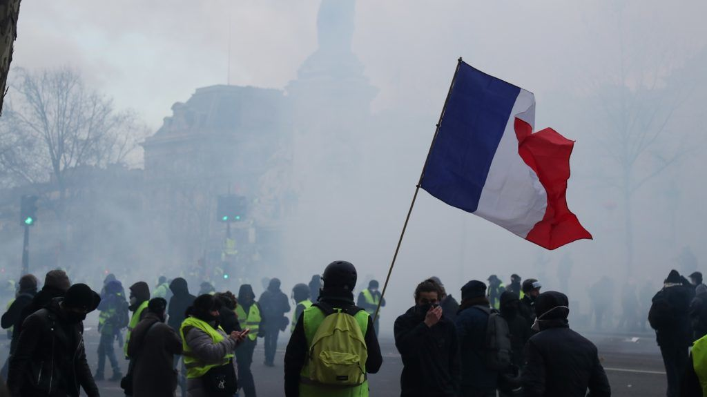 A yellow vest protester (Gilets Jaunes) waves a French flag on the Place de la Republique in Paris on February 2, 2019, on the sidelines of a march called to pacifically protest against police violence toward participants of the last three months demonstrations in France, as yellow vest protesters (Gilets Jaunes) take to the streets for the 12th consecutive Saturday. - The 'Yellow Vest' (Gilets Jaunes) movement in France originally started as a protest about planned fuel hikes but has morphed into a mass protest against President's policies and top-down style of governing. (Photo by Zakaria ABDELKAFI / AFP)
