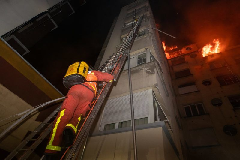 """This handout picture taken and released by the Paris firefighters brigade in the night of February 5, 2019 shows a fireman climbing up a ladder as a fire burns in a building in Erlanger street in the 16th arrondissement in Paris. - A woman has been arrested over a deadly blaze that killed eight people in Paris and police are treating the fire as a possible arson attack, a prosecutor said early on February 5. (Photo by HO / BSPP - Brigade de sapeurs-pompiers de Paris / AFP) / RESTRICTED TO EDITORIAL USE - MANDATORY CREDIT """"AFP PHOTO / BSPP"""" - NO MARKETING NO ADVERTISING CAMPAIGNS - DISTRIBUTED AS A SERVICE TO CLIENTS ---"""