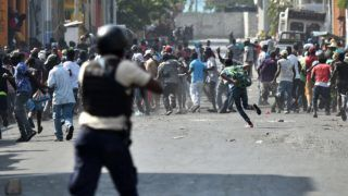 Demonstrators flee as Haitian Police open fire, during the clashes, in the centre of Haitian Capital Port-au-Prince, February 13, 2019. - This is the seventh day of protests against Haitian President Jovenel Moise and the misuse of the Petrocaribe fund. (Photo by HECTOR RETAMAL / AFP)