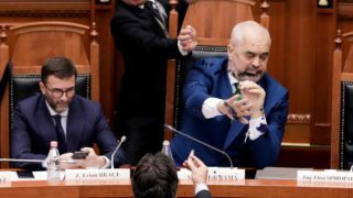 Albanian opposition member of Parliament Edi Paloka throws ink at Albanian Prime Minister Edi Rama (R) during a parliamentary session in Tirana on February 14, 2019. - Following the incident, the National Guard removed MP Edi Paloka from the session. (Photo by STRINGER / AFP)