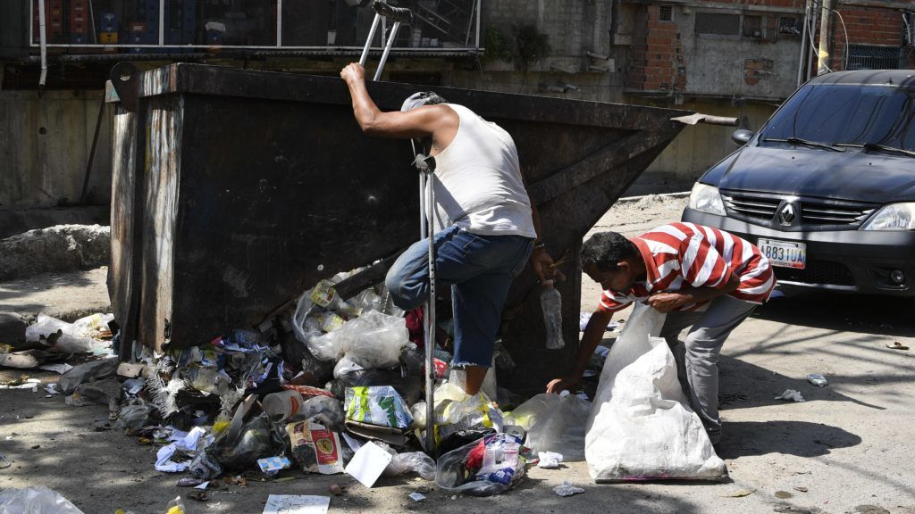 An amputated man looks for recyclable plastics in a garbage container in Caracas, on February 17, 2019. - Venezuelan opposition leader and self declared acting president Juan Guaido set a goal Sunday of enlisting a million volunteers within a week to confront a government blockade that has kept tons of humanitarian aid, most of it from the United States, from flowing into the country. (Photo by Yuri CORTEZ / AFP)