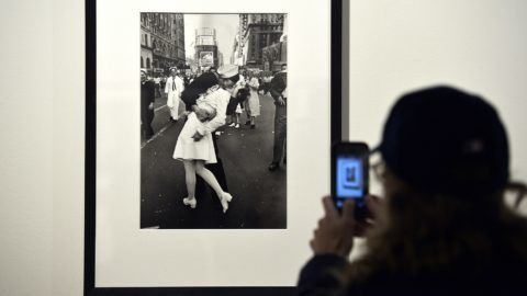 """(FILES) In this file photo taken on April 30, 2013 a visitor takes a snapshot of """"VJ Day in Times Square, New York, NY, 1945"""" by Alfred Eisenstaedt during the """"Life, I grandi fotografi"""", (The great photographers) exhibition at the auditorium in Rome. - The sailor pictured kissing a woman in Times Square as people celebrated the end of World War II has died at age 95, his daughter told the Providence Journal. George Mendonsa had a seizure February 17, 2019 after falling at an assisted living facility in Middleton, Rhode Island, his daughter Sharon Molleur said. In the famous image, one of four taken by Alfred Eisenstadt for Life magazine, Mendonsa is seen ecstatically bending over and kissing a woman in a white nurse's uniform.The picture was published by Life as """"V-J Day in Times Square."""" (Photo by Gabriel BOUYS / AFP) / RESTRICTED TO EDITORIAL USE - MANDATORY MENTION OF THE ARTIST UPON PUBLICATION - TO ILLUSTRATE THE EVENT AS SPECIFIED IN THE CAPTION"""