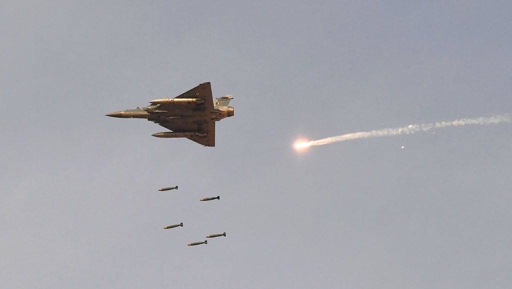 """In this photo taken on February 16, 2019, an Indian Air Force (IAF) Mirage-2000 fighter aircraft drops bombs during the 'Vayu Shakti 2019' fire power demonstration at the IAF's firing range field in Pokhran in the state of Rajasthan. - An Indian air strike across the Kashmir ceasefire line early February 26 """"completely destroyed"""" a militant camp, a junior minister said. (Photo by Prakash SINGH / AFP)"""