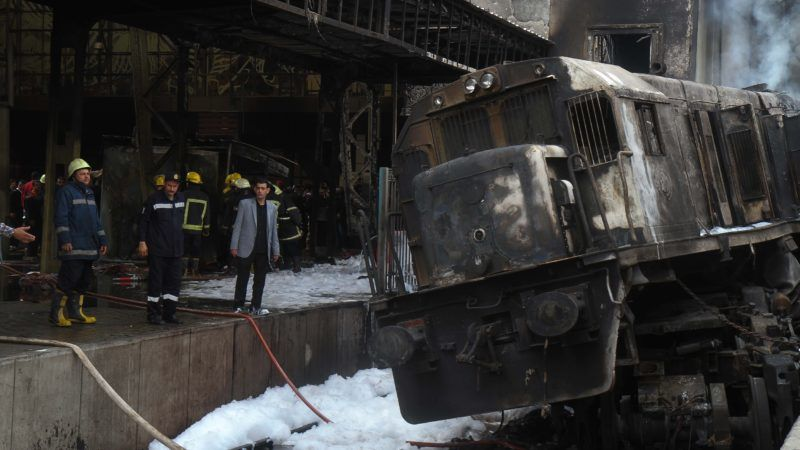 """Fire fighters and onlookers gather at the scene of a fiery train crash at the Egyptian capital Cairo's main railway station on February 27, 2019. - The crash killed at least 20 people, Egyptian security and medical sources said. The accident, which sparked a major blaze at the Ramses station, also injured 40 others, the sources said. (Photo by STRINGER / AFP) / """"The erroneous mention[s] appearing in the metadata of this series of photos by STRINGER has been modified in AFP systems in the following manner: [STRINGER ] instead of [Hussein Talal]. Please immediately remove the erroneous mention[s] from all your online services and delete it (them) from your servers. If you have been authorized by AFP to distribute it (them) to third parties, please ensure that the same actions are carried out by them. Failure to promptly comply with these instructions will entail liability on your part for any continued or post notification usage. Therefore we thank you very much for all your attention and prompt action. We are sorry for the inconvenience this notification may cause and remain at your disposal for any further information you may require."""""""