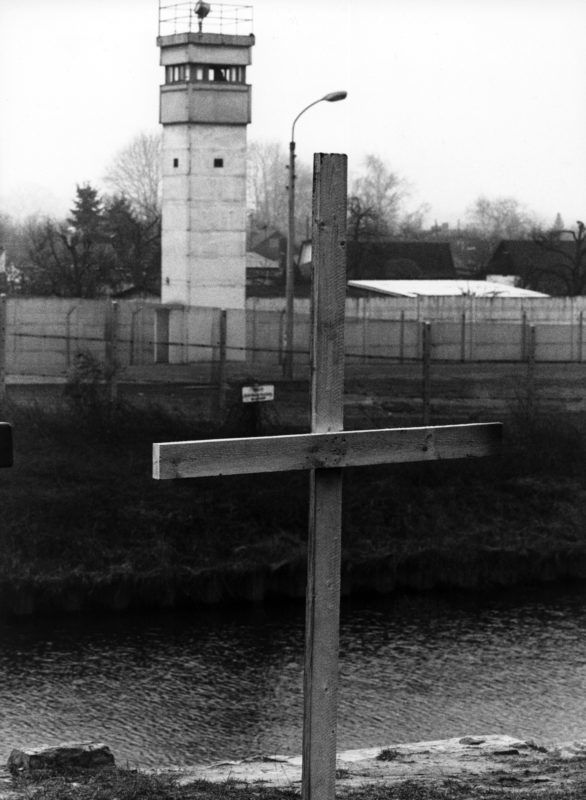 """FILED - 23 February 1989, Berlin: A simple wooden cross in front of the Teltow Canal in the district of Neukölln reminds of Chris Gueffroy, who was shot by GDR border guards. 30 years ago, on 5 February 1989, the young East Berliner died when he wanted to overcome the border fortifications with a friend. (to """"Chris Gueffroy: Last shot refugee at the Berlin Wall"""" on 02.02.2019) Photo: Fotoreport-DB/dpa"""