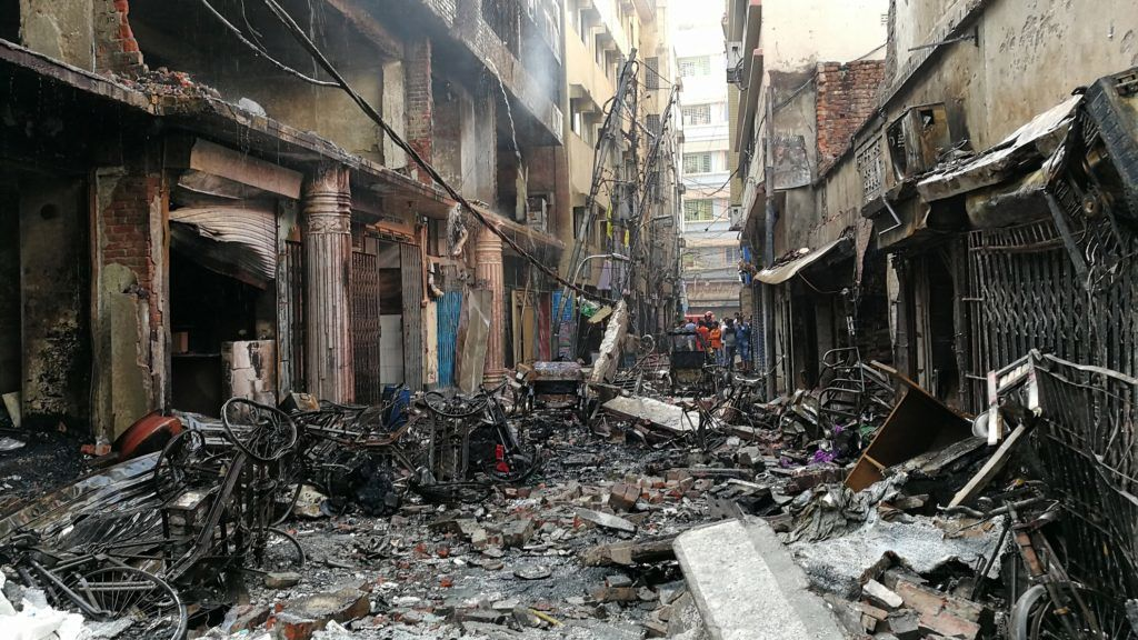 21 February 2019, Bangladesh, Dhaka: After a major fire, rubble is lying on a street in front of buildings destroyed by flames. Dozens of people lost their lives in a major fire in Bangladesh's capital Dhaka. This was said on Thursday morning 21.02.2019 by Kamrul Hasan, the officer on duty of the fire brigade and civil defence, to the German Press Agency. Photo: Mohammad Al-Masum Molla/dpa