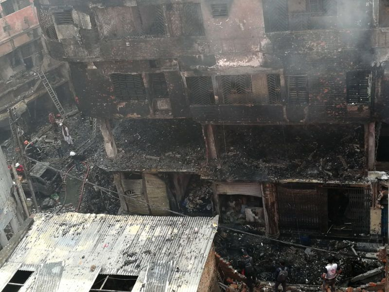 21 February 2019, Bangladesh, Dhaka: After a fire, people stand near a building destroyed by the flames. Dozens of people lost their lives in a major fire in Bangladesh's capital Dhaka. This was said on Thursday morning 21.02.2019 by Kamrul Hasan, the officer on duty of the fire brigade and civil defence, to the German Press Agency. Photo: Mohammad Al-Masum Molla/dpa