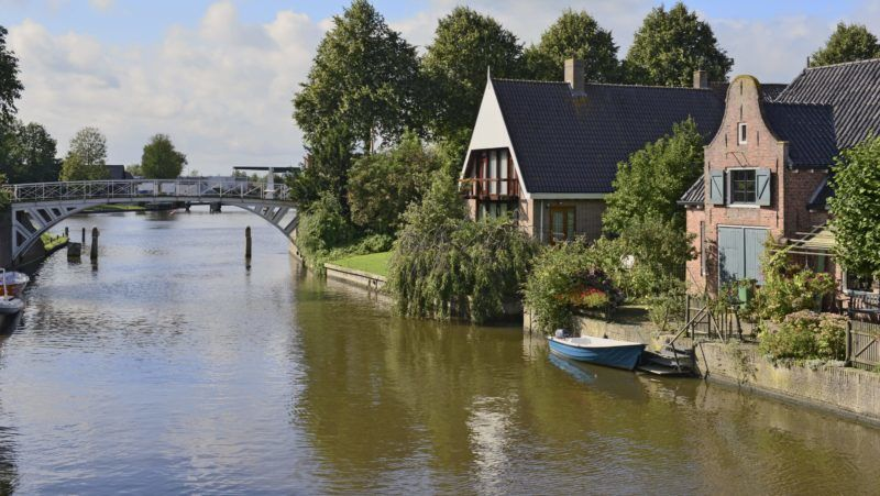Pedestrian bridge and houses at the canal Klein Diep with a boat on the water in th town Dokkum, 7 September 2015 | usage worldwide